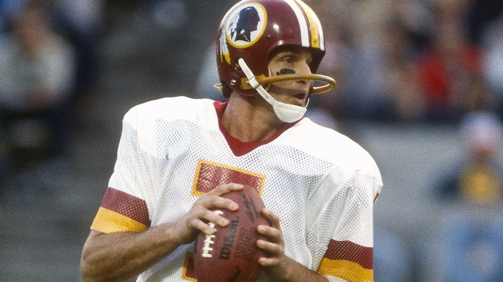 Joe Theismann in action with the Washington Redskins. One of the best quarterbacks of the 1980s, Theismann led his team to victory at Super Bowl XVII and the NFC championship the following year. A severe leg injury in 1985 put an end to his playing days, but the undeterred athlete and lover of the game went on to a successful career in broadcasting.