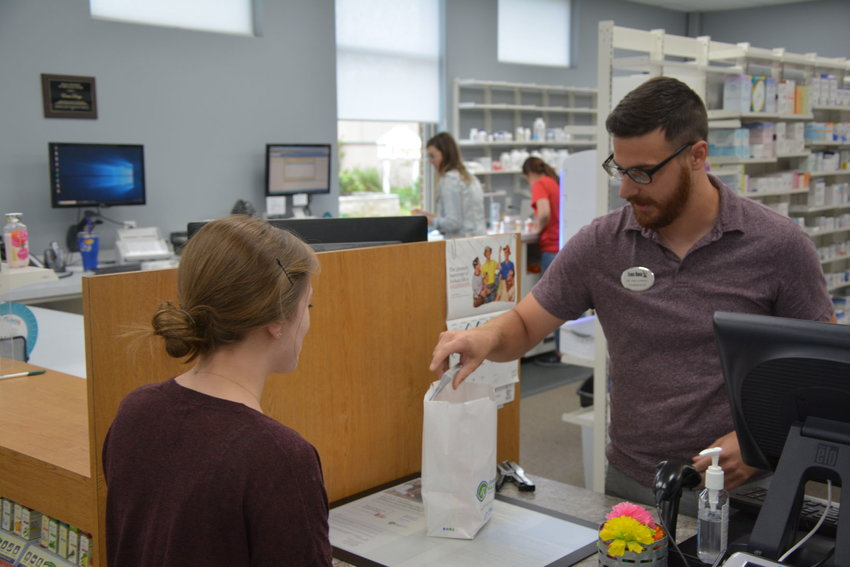 Jake Gorrell discusses a prescription with a customer at Evans Drugs.