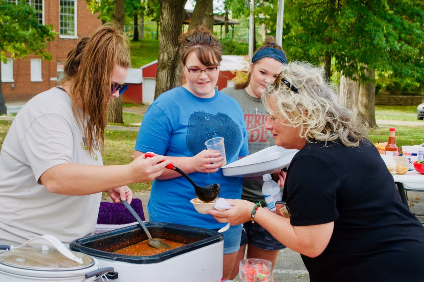 Peyton Newman, left, serves a heaping bowl of chili to Mary Martin at the Wayside Inn Museum's first annual chili cook off Saturday, Oct. 9.