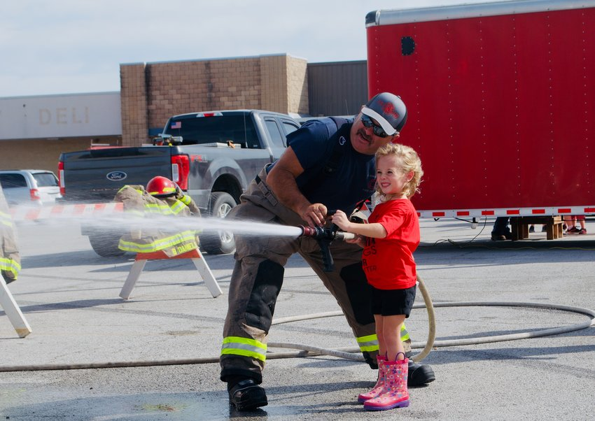 The El Dorado Springs Volunteer Fire Department, Citizens Memorial Hospital and more were on deck at the Shopko parking lot Saturday, Oct. 9, for the Junior Firefighter event, which allowed kids to learn about fire safety, tour firetrucks and ambulances, try on firefighter apparatus, test out water hoses and even check out a bounce house. Pictured, Nora Gadea aims for a pretend flame with a spurt of water.