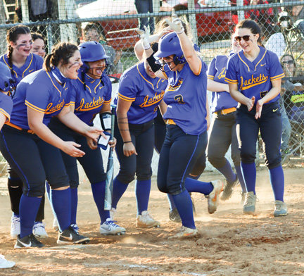 Kylie Minick is celebrated by teammates as she approaches homeplate after hitting a three-run homer during the March 29 game against Harding Academy.