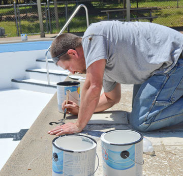 Mountain View city employee Josh Lawson puts finishing touches on some paint detail work at the city swimming pool.