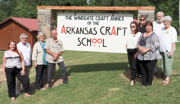 Arkansas Craft School Executive Director Rachel Reynolds, at left, with board members (from left) David Ciscel, Gin Brown, Stan Brown, Maegon Mayes, Lynn Nancarrow, Dorothy Lanning, Bud Thurman and Joy Harp at the annex location. The sign is an art piece in progress.