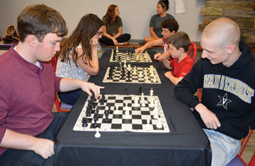 In foreground, Nate Franks and Will Fowlkes are among those participating in Chess Night at the Stone County Community Center.