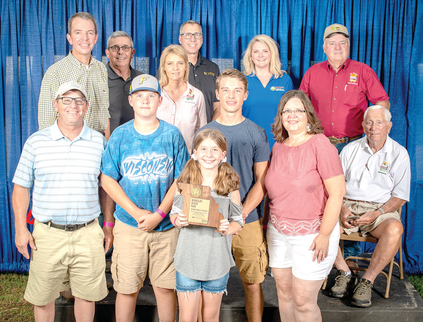 The Juergensmeyer family was selected as the 2019 Osage County Farm Family after voting by the Osage County Extension Council and local Farm Bureau, and honored Monday, Aug. 12 at the Missouri State Fair. Members of the Juergensmeyer family are, from left to right, Kaylee (holding the plaque), John, Greyson, Braden and Janel; shown with the family are MU Extension and Engagement Vice Chancellor Marshall Stewart, Missouri Farm Bureau President Blake Hurst, 2018 State Fair Queen Samantha Nelson, State Fair Commissioners, Nikki Whitehead and Ted Sheppard, Director of Missouri Dept. of Agriculture Christine Chin, ; and MU College of Agriculture, Food and Natural Resources Dean Christopher Dauber.