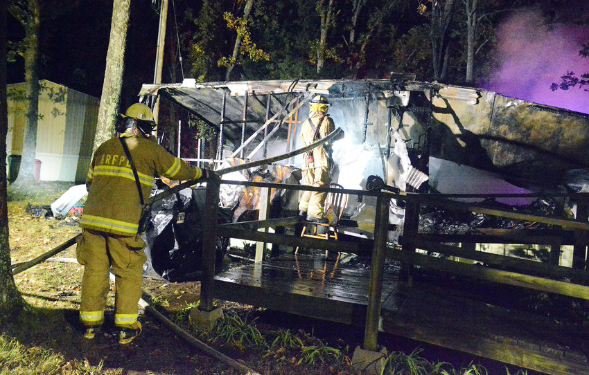 FIREMEN battled an accidental fire early Oct. 23 which destroyed a mobile home in the Rolling Homes park.