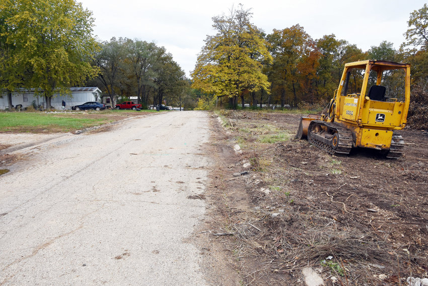 """OLIVE STREET looking west into the former """"Grove"""" trailer park from the portion of the nearly 9-acre tract which has been cleared recently. Nine of the 10 mobile homes on the site are currently occupied. The tenth was abandoned, a neighbor said, due to damage from a water leak."""