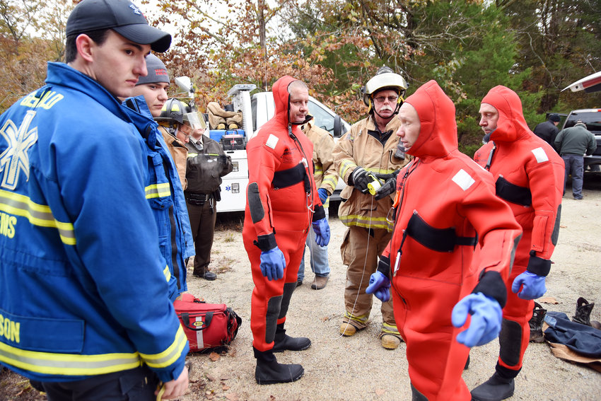GERALD AREA Ambulance District's Jordan Acre (left) and Curtis Peffermann listen as Owensville Fire Chief Scott Strang­hoener explains the plan for firemen wearing cold water rescue gear to retrieve the body of Bernard F. Mahacek and carrying him out using a rescue basket. Firemen Carl Smith, Charles Ammermann and Jeff Limberg are also shown.