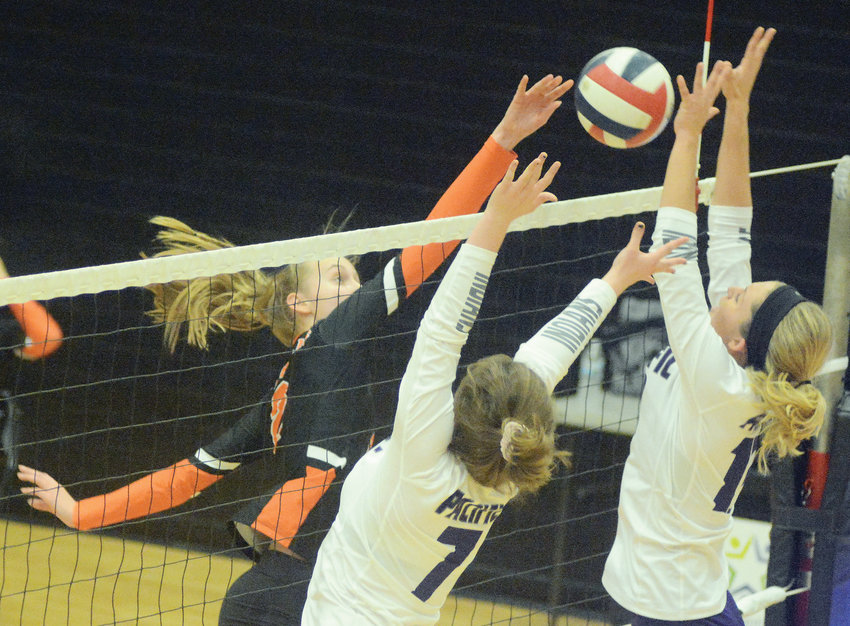 Emily McKinney (above, left) spikes the ball off the hands of a Pacific defender for a point during Owensville's first-round MSHSAA Class 3, District 8 volleyball match against Pacific back on Monday, Oct. 28 at Sullivan High School.