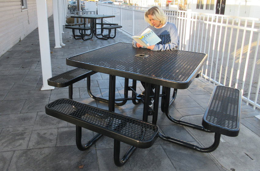 Vienna library worker Amanda Kremer is pictured at one of the five new tables on the patio located on the east side of the building on Main Street. All of the tables were paid for by donations.