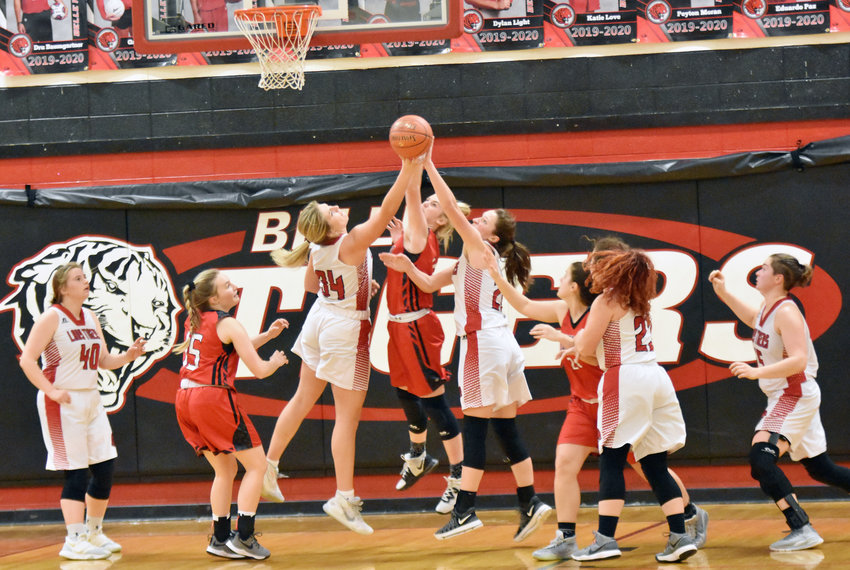 Halle Smith and Olivia Sanders (above, center) battle for a rebounds for Belle's Lady Tigers during their 58-55 loss Thursday night at home in a Highway 28 showdown against Dixon's Lady Bulldogs.