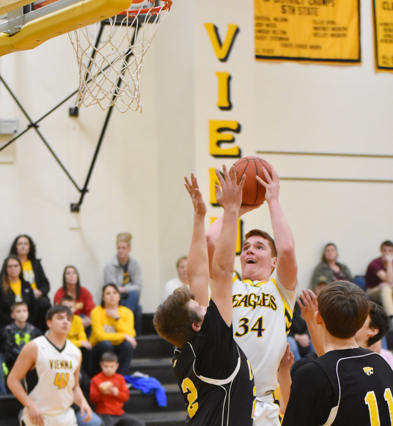 Daniel Casey (above, center) goes up for a shot against Cuba Friday night for the host Eagles at Vienna High School.