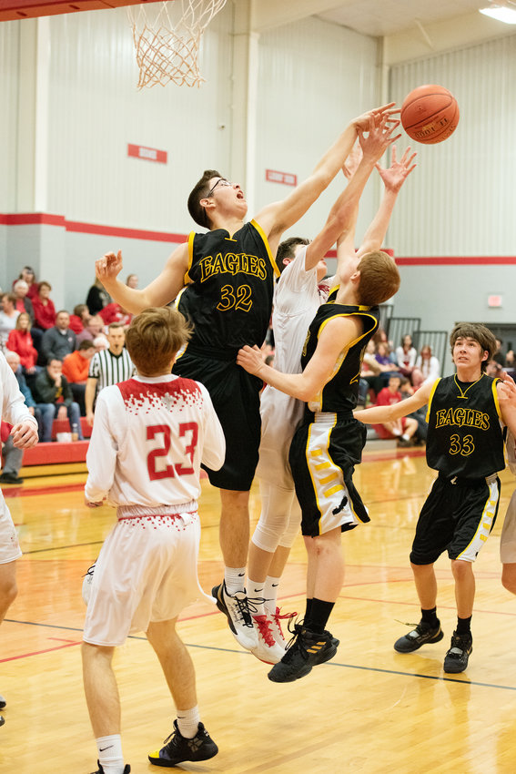 Josh Casey (second from left) goes up to deflect a pass during Vienna's 63-35 road loss in junior-varsity action against the Lions in Jefferson City.