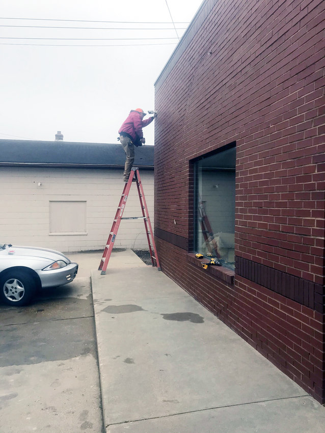 Central Electric technicians Adam McKay (above, left) and Cyle Martin (above, right) are shown installing two of the seven new security cameras at Squeaky Clean Laundry in Gerald. The business has been plagued with vandalism in recent months. Dryer doors have been kicked off and the bathroom has been soiled.