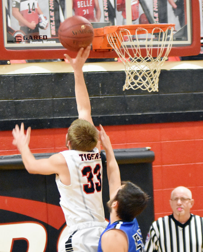 Jat Ridenhour (left) puts in two of his game-high 18 points for the Tigers in their 71-22 win over the Blue Jays completing Belle's sweep of Friday's pink-out basketball doubleheader.