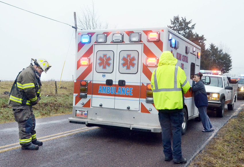 Peering into an Ozark Central ambulance, Danielle Taylor had pleaded moments before for information about her boyfriend, Cody J. Smith, who had died Feb. 12 in a one-car crash on Route M. Belle's assistant fire chief, Nathan Abel (left),  had command of the recovery effort completed moments earlier.