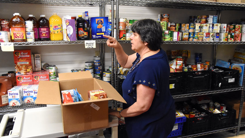 A SHELF STABLE box of food was being prepared (far left) by Nowack which was later delivered to a disabled man near Fredericksburg. The local senior center was assisting another agency with an emergency supply of food stocks due to delivery conditions created by the COVID-19 pandemic threat and service interruptions.