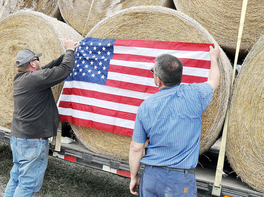 Jimmy Zumwalt (left) attached a flag to a hay bale before the first trip to Kansas trip in March of 2017.