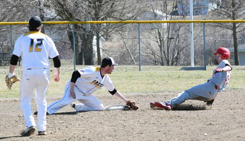Logan Agan (above, center) sticks his golve right in front of second base before tagging out a would-be base runner during his senior season last spring in a Vienna High School baseball uniform under former head coach Tyler Shalbot.