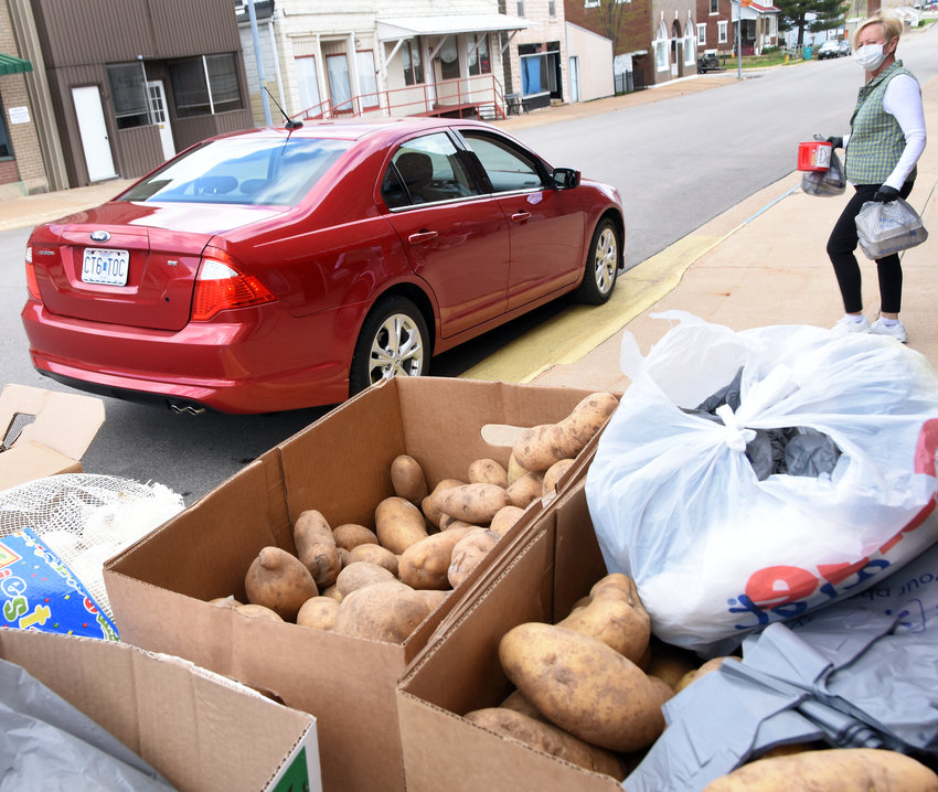CURBSIDE MEAL delivery at Owensville Senior Center included periodic sidewalk market opportunities for area seniors. Food stocks including potatoes were available during the April 15 pickup period.