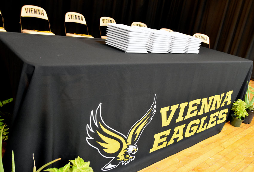 A table draped with a Vienna Eagles tablecloth with diplomas stacked on top at the 2019 Vienna High School graduation ceremony.