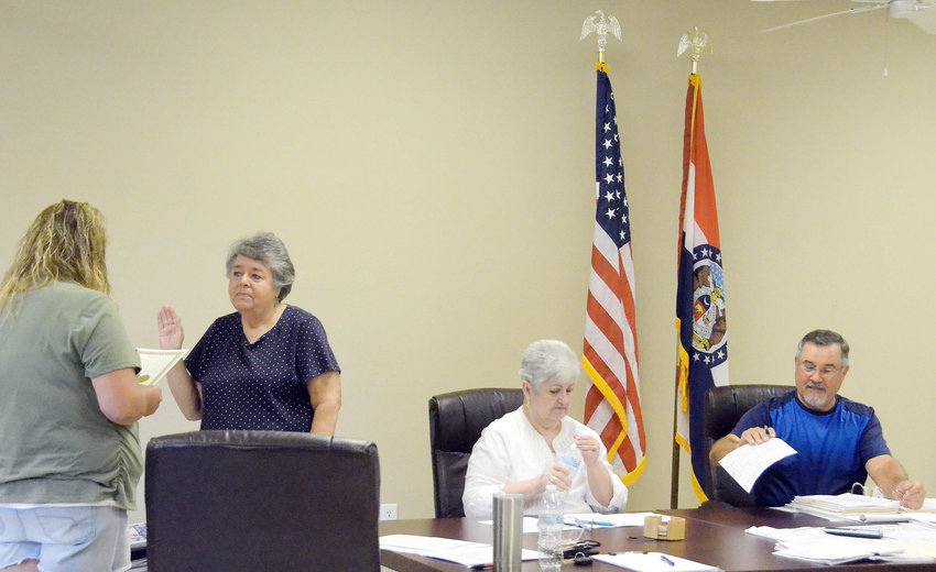 Bland city Clerk Carrie Krupp (above, left) swears in Alderman Jane Vandegriffe after swearing in Mayor Lee Medlock (far right) at the June 8 meeting. A second alderman position is still available. Interested parties can contact the administration building for more information. Alderman Sherry Spradling (center) glances over city business.