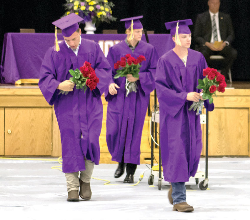 David Carter, Brandon Dodson and Eli Cole head toward family and friends to present roses during Chamois graduation.