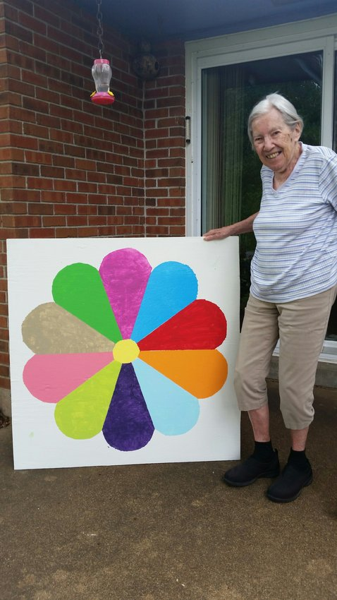 Pauline Bescheinen is pictured with the Dresden Plate barn quilt she painted.