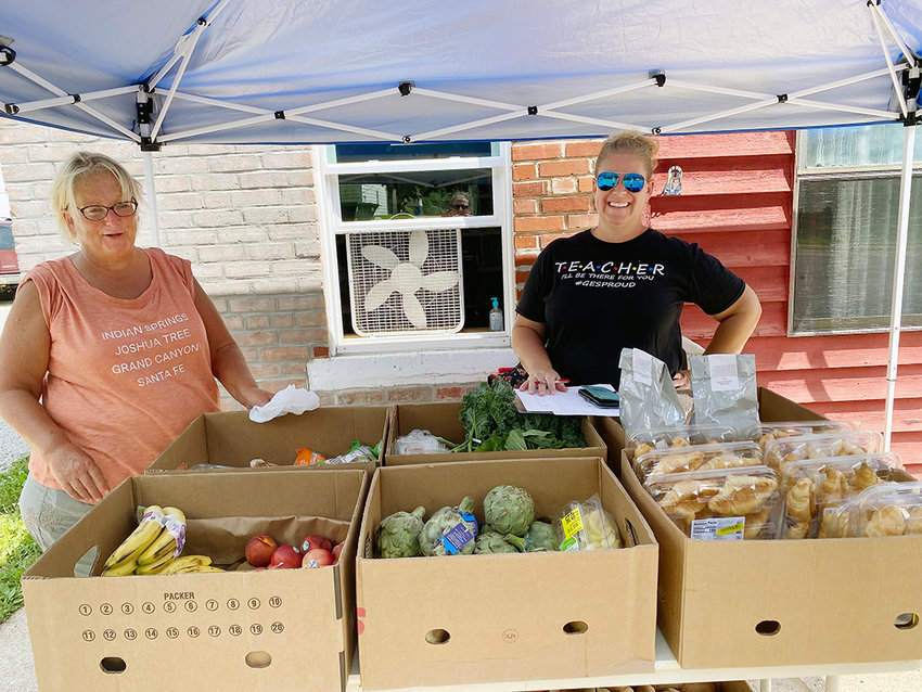 GES teachers Lauri Link (above, left) and Stephanie Royle manned the stand at Gerald's Community Outreach Monday. They assisted families who stopped by to get a meal for their kids through the summer lunch program.  The two teachers also helped distribute produce for anyone in the community.