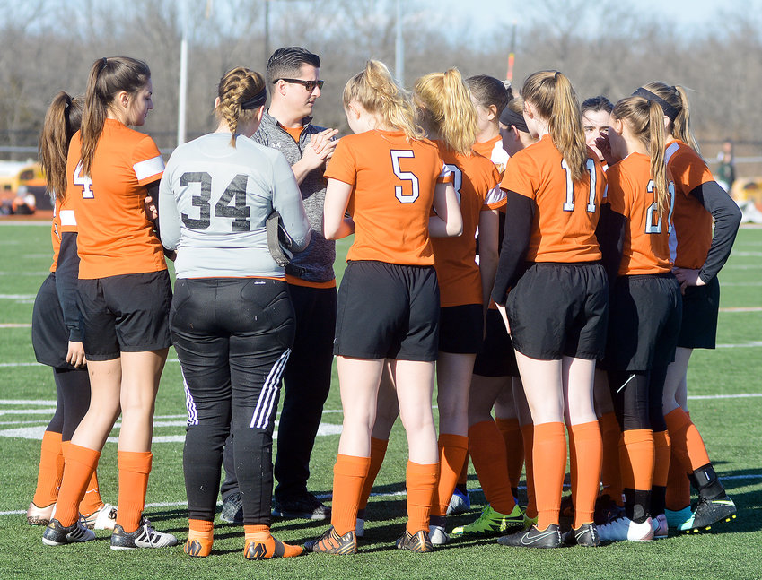 Jordan Palmer (above, third from left) led his Owensville Dutchgirl soccer team in a pregame huddle during the spring 2019 season. This past spring's season was canceled due to the COVID-19 pandemic. Starting the program in the spring of 2014, Palmer finished with a record of 42-56-1 during his six seasons as Dutchgirl head soccer coach. Palmer will continue to teach instrumental music and band classes in the district going forward.