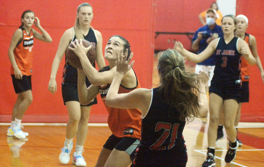 Anna Skornia (center) attacks the basket with teammates (from left) Emma Daniels and Kate Angell looking on.