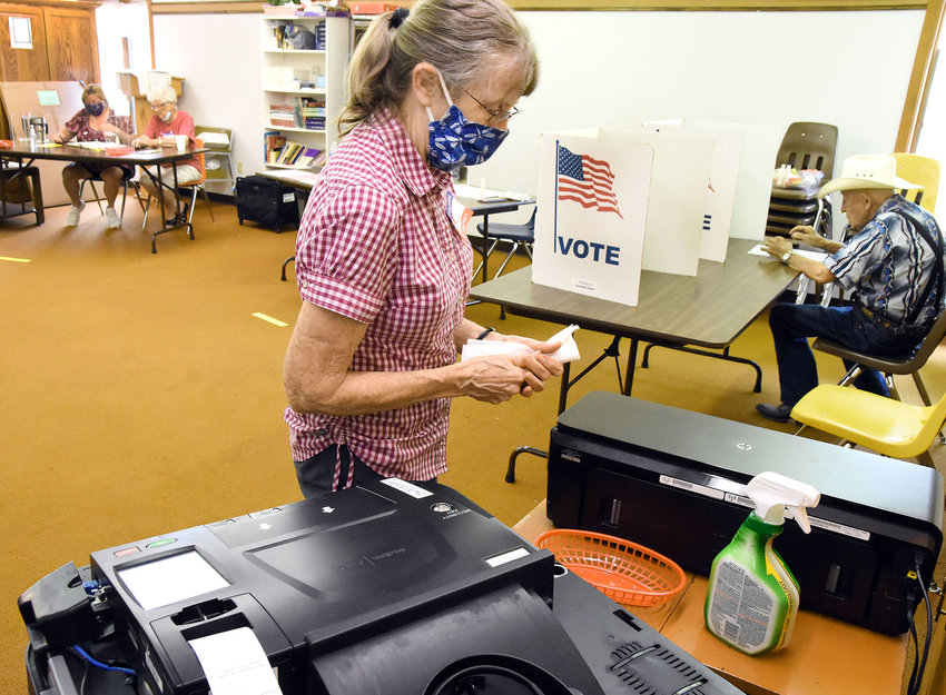 Owensville Ward 2 election judge Ruth Rebmann disinfects markers used by voters Tuesday in the Primary Election.  Judges were protected by a plexiglass screen and had the option of wearing face masks. Turnout across the county was 40 percent.
