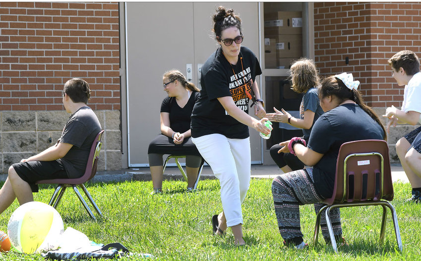 """Owensville Middle School teacher Miranda Schultz squirts hand sanitizer for students Tuesday afternoon during an outdoor classroom setting game of """"Quiet Ball on Steroids"""" as part of summer school. """"And I had to sanitize to be safe!"""" said Schultz."""