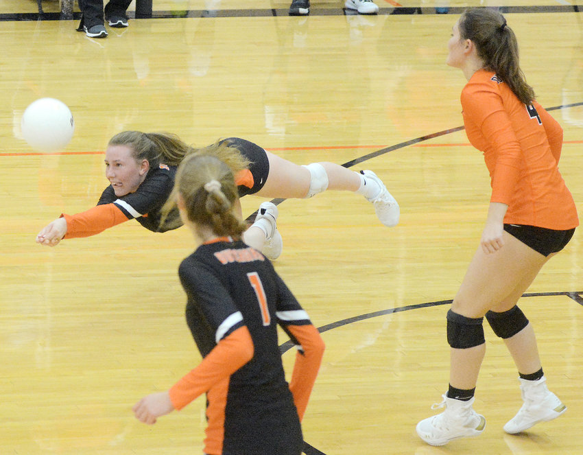 Grace McFalls (above, horizontal) lays out to keep the volleyball from hitting the floor during Owensville's season-opening victory in three sets Monday night over Linn by scores of 25-11, 25-8 and 25-11. Fellow Dutchgirl volleyball players watching McFalls herculean effort were Emily McKinney (1) and Cadi Ruth (far right).