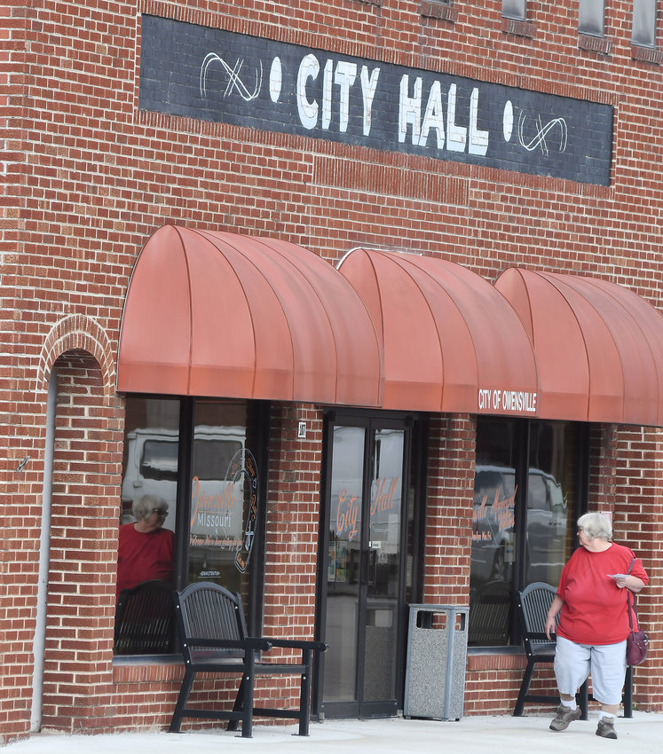 "A WOMAN who dropped off a utility payment reads the closed sign on the City Hall door on Monday. The message included the note: ""We apologize for any inconvenience and appreciate  your understanding during these unprecedented times."""
