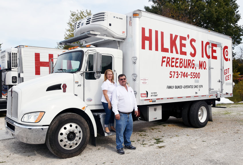 Laron and Donna Hilke stand with one of their many delivery trucks.