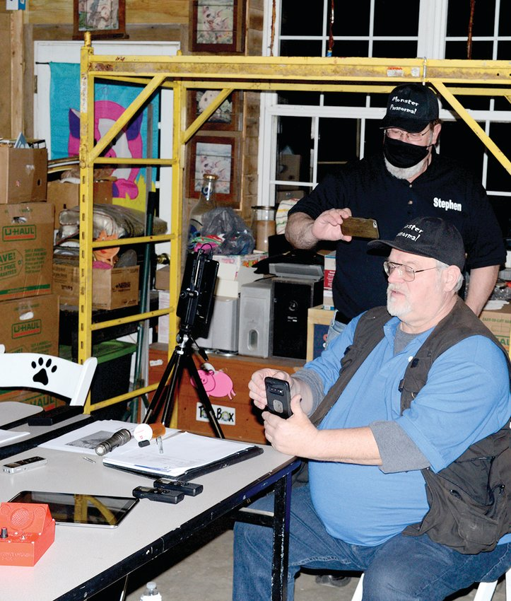 Ken Raumoeller (seated) and his partner, Stephen Lange, check equipment for an electrical representation of spirits at Where Pigs Fly during a recent event.