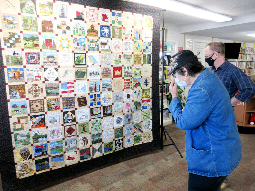 Lucy Branson of Vienna, and Michael Sweeney, State Historical Society of Missouri Bicentennial Coordinator, look at the beautiful Bicentennial Quilt while it was at the Vienna Library last Thursday afternoon and evening.