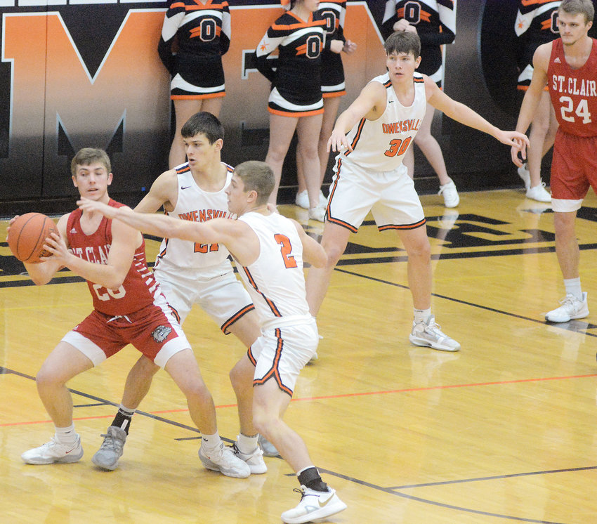 Dutchmen defenders (from left) Derek Brandt, Brendan Decker and Tyler Heidbrink keep their eyes on the basketball during the consolation championship game against St. Clair Saturday afternoon at the 32nd Owensville Varsity Boys Basketball Tournament.