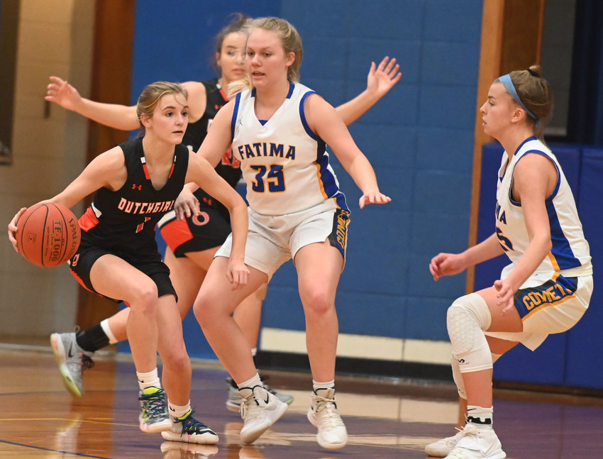 Emma Daniels (left) looks to navigate her way through the defense of the Fatima Lady Comets Thursday night on the road in Westphalia.