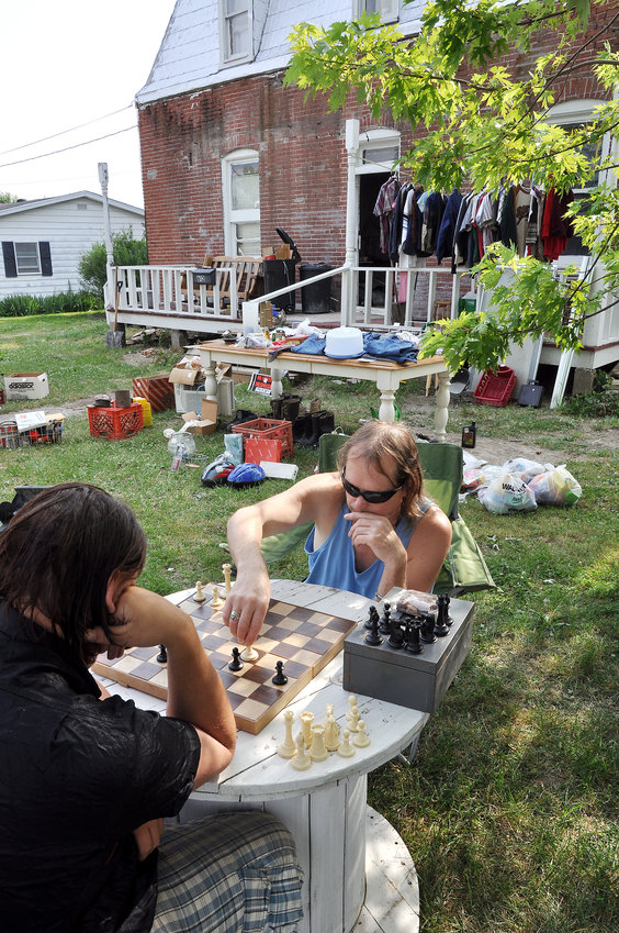 Glen Fawcett plays chess with a friend in May of 2012 during a yard sale held in an attempt to raise funds for porch and house repairs at 612 South First. He lived there but did not own his family's residence. Police conducted an inspection that day which resulted in a city-ordered cleanup of the flooded basement.