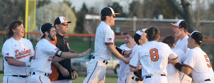 Owensville Dutchmen baseball players mob Dominic Grigaitis (hidden, far right) after his walk-off double in the bottom of the eighth inning gave OHS a 6-5 victory over Hermann's Bearcats in eight innings Monday night at OHS Field.