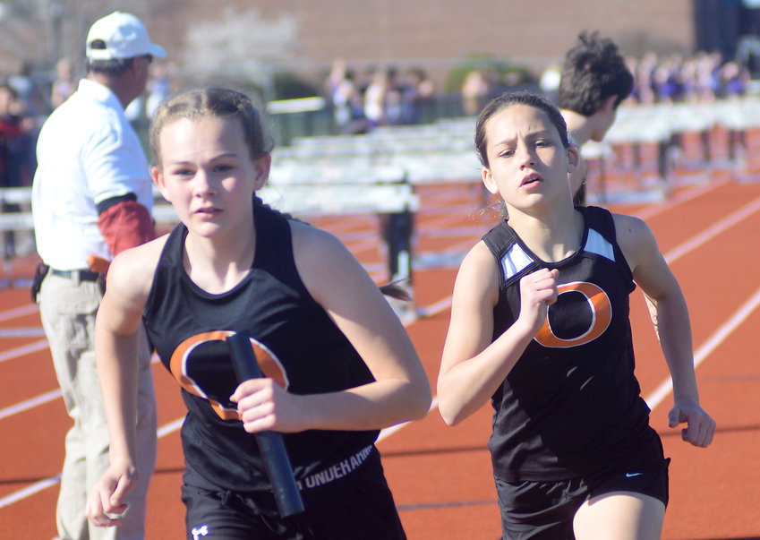 Lauren Kandlbinder (left) takes off with the baton from Ilene Limberg during the girls 4x800-meter relay at last Monday's Owensville Middle School quad track meet at Dutchmen Field.
