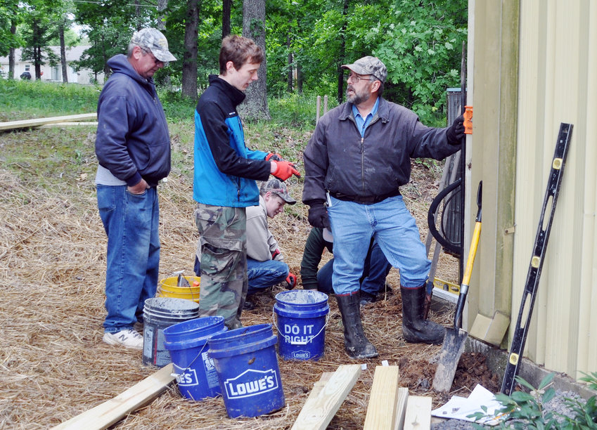 Michael Lowes (center) discusses his Eagle Scout project with Paul Stillman as Ed Voss listens. Colten Baird-Halsey and Hunter Colombo (partially hidden) work in the background. Voss and Stillman are former Scout leaders. The group was constructing a barrier around the air conditioning units at the Gerald Lions hall.