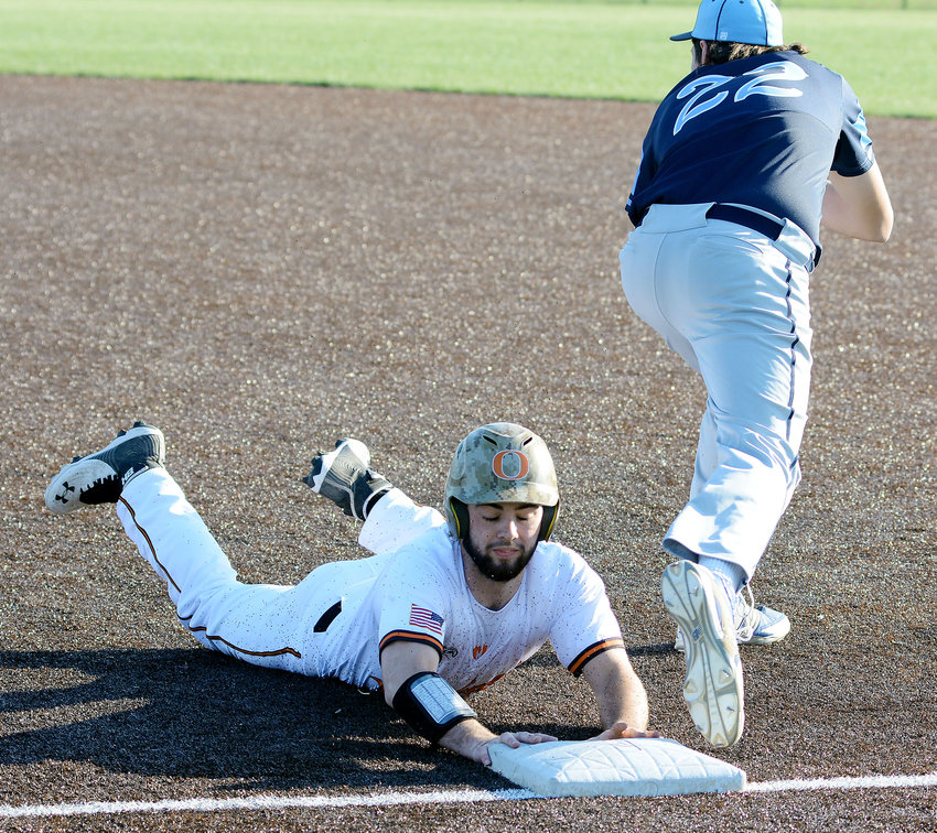 Garret West (left) slides safely back into first base during an attempted pick off in late March baseball action at OHS Field against Salem's Tigers.