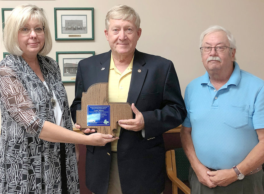 Executive Director Bonnie Prigge (left) presents Gasconade County Presiding Commissioner Larry Miskel with a plaque recognizing his service as board chair. Steve Vogt with city of Belle (right) took over chairman responsibilities at the June meeting.