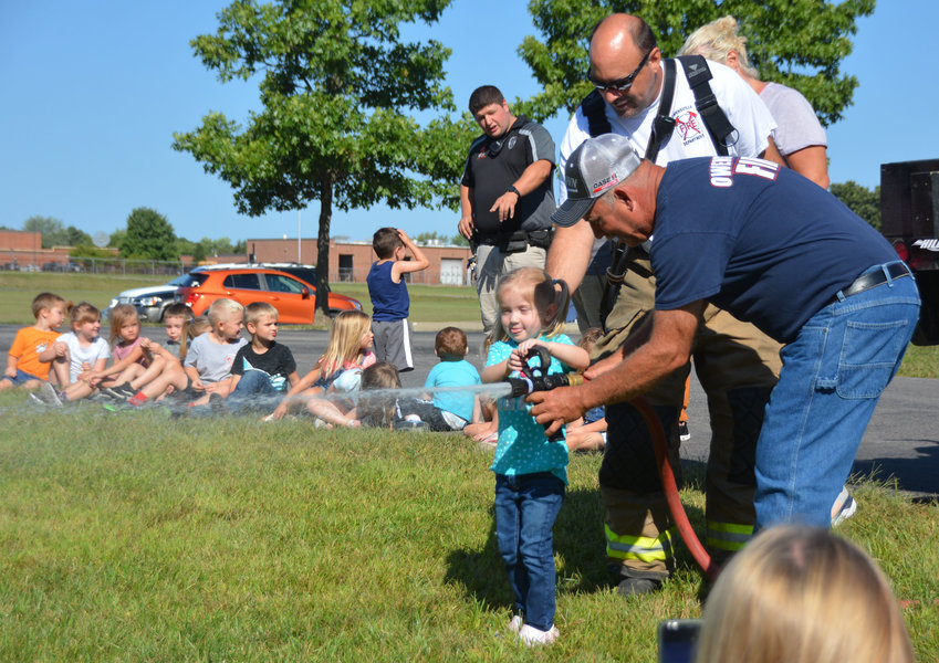 Rylee Shockley, an Owensville Elementary School preschool student, flows water from an Owensville Fire Department  hose Thursday under the supervision of volunteer firemen Assistant Chief Jeff Limberg and Chief Jeff Arnold (in back). Firemen were at the school with other emergency services agencies last week for programs about community leaders.