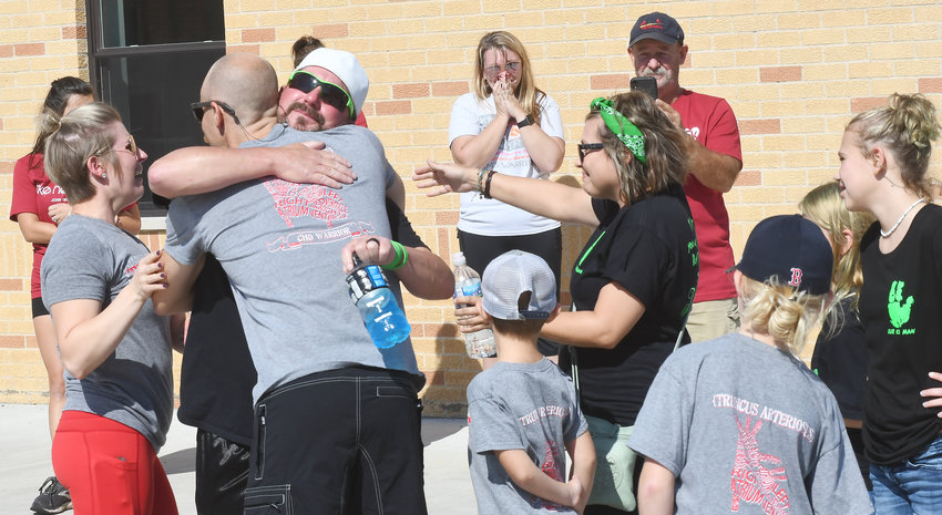 """Donor family meets recipient's family at 'Celebrate Life' event. Their families — linked forever by a bond few could image — met for the first time Sunday during a """"Surprise 5K"""" walk and run in Owensville to benefit the Mid-America Transplant program's Celebrate Life campaign. Chris McDougald, Lebanon, Mo., (facing camera) embraces Brett Palmer of Owensville as their respective wives, Danielle Palmer (left) and Stephanie McDougald reach out to greet each other with a hug. The McDougald's son, Ki, 3, died Oct. 29, 2019, from injuries in a """"freak"""" all-terrain vehicle crash three days earlier. The Palmer's son, Truett, born with a genetic heart condition, received Ki's heart the following day. Truett would live another year before what was described by his mother as a common """"bug"""" caused his death on Nov. 3, 2020. The Palmers had been at their's son's one-year transplant checkup when he fell ill. Truett's transplanted heart from the McDougald's son was healthy. A """"common ailment"""" causing a lung infection was cited as his cause of death at the age of 3 years and 8 months. As friends and family of the Truetts waited to begin the 5K fund-raiser, the families of two boys — forever linked together through organ donation — embraced. Then walked together."""