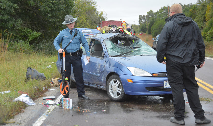 Missouri State Highway Patrol Cpl. Coby G. Holzschuh takes measurements Friday morning at the scene of a one-car roll-over crash on Highway 28 for his report.