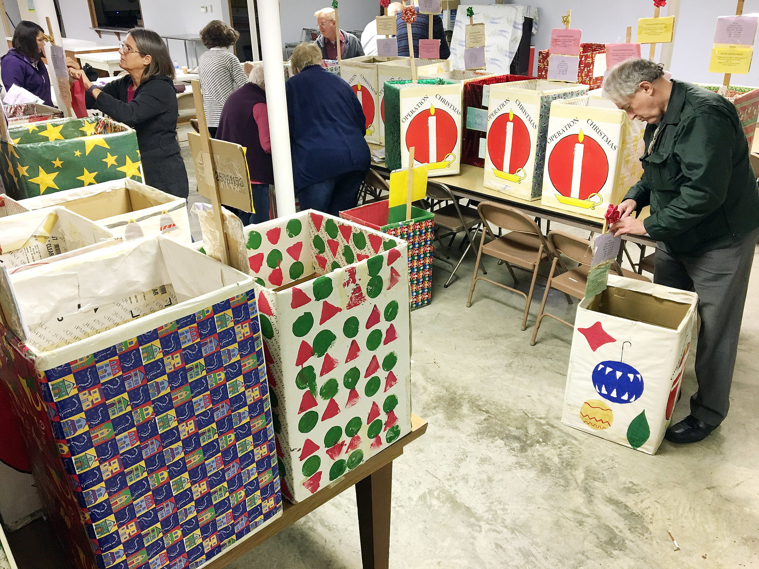 ST. PAUL UCC Pastor Stephanie DeLong and Bob Duda were among Operation Christmas volunteers repairing food collection boxes Monday.